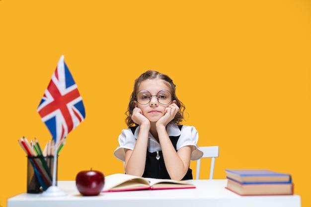 Colegial caucasiana entediante e triste sentada na mesa com livros, aula de inglês, bandeira da grã-bretanha