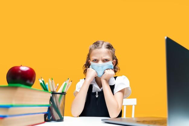 Colegial caucasiana triste com raiva usando máscara médica e estudando em casa com ensino à distância em laptop