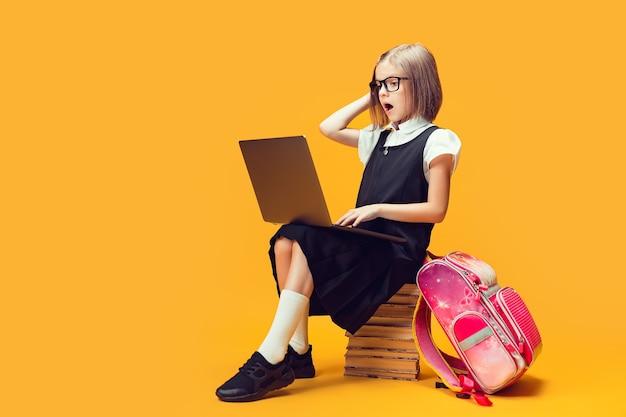 Colegial chocada de corpo inteiro sentada na pilha de livros, trabalhando no laptop, crianças, conceito de educação