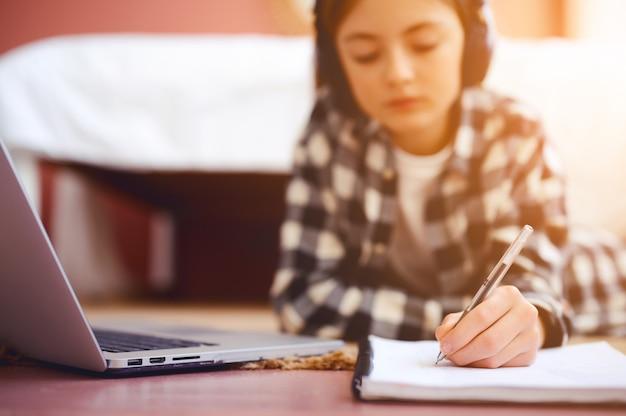 Colegial com fones de ouvido digitando no notebook perto de laptop