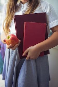 Colegial, com, maçã, e, livros, em, mãos