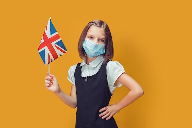 Colegial com máscara médica protetora com bandeira britânica em um conceito de segurança de fundo amarelo