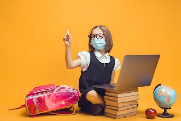 Colegial com máscara sentada atrás de uma pilha de livros e um laptop levantando o dedo indicador para a educação infantil