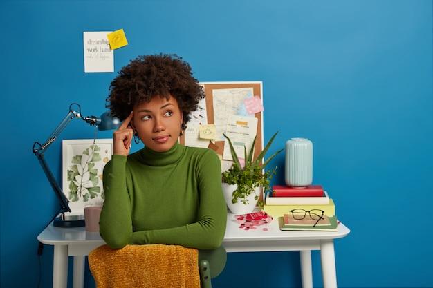 Colegial de cabelo encaracolado habilidosa e pensativa olha de lado, tem uma expressão pensativa, mantém o dedo indicador na têmpora, vestida com roupas casuais, senta-se no espaço de coworking contra a mesa com as coisas necessárias