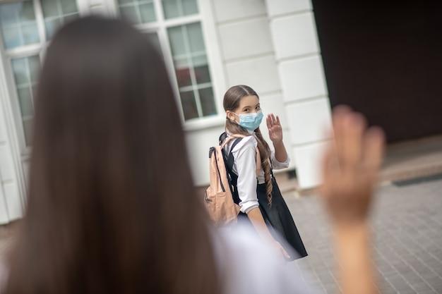 Colegial de cabelos compridos com mochila e máscara protetora se despedindo da mãe perto da escola levantando a mão