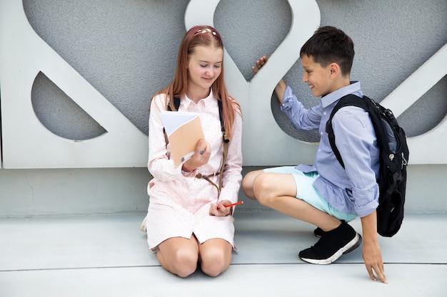 Colegial e colegial flertando olhando um para o outro na rua do pátio da escola