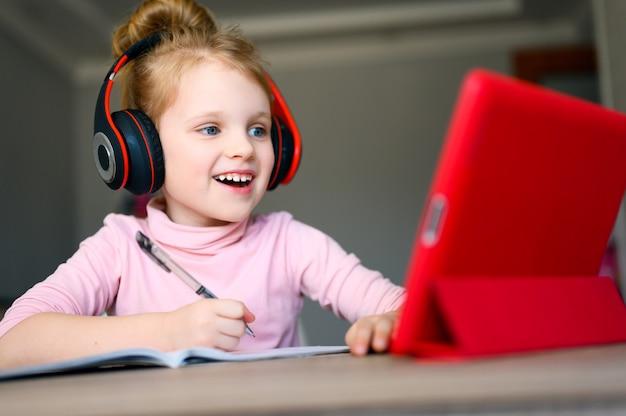 Colegial em fones de ouvido, estudando em casa com tablet digital, sorrindo e fazendo lição de casa da escola.