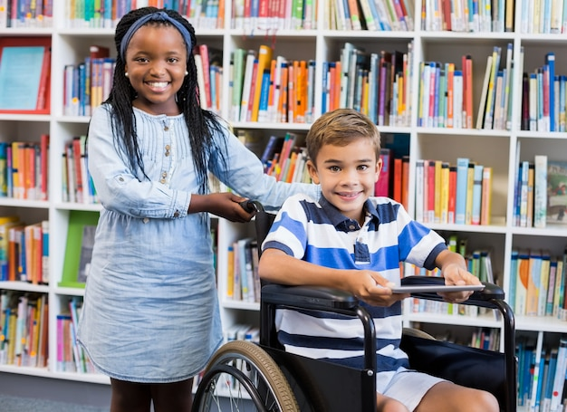 Colegial feliz em pé com o aluno na cadeira de rodas