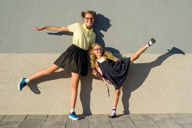 Colegial irmãs bonitos em uniforme escolar.