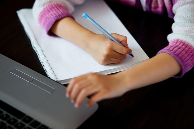 Colegial irreconhecível estudando em casa com um notebook e fazendo lição de casa da escola.