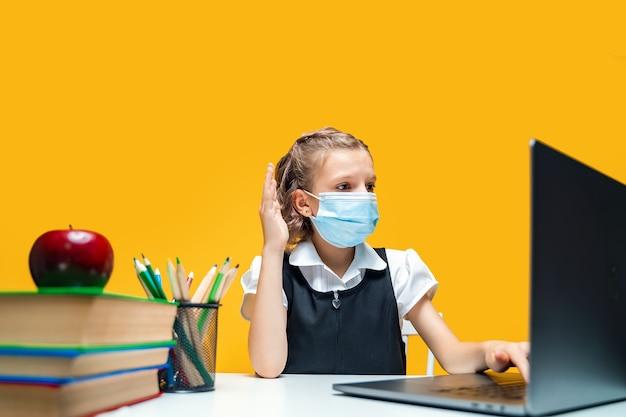 Colegial levantando a mão e sentada no laptop usando máscara amarela, aprendizagem à distância de fundo
