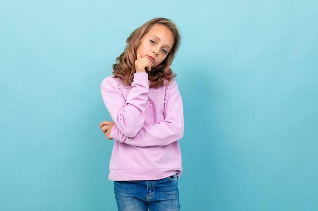 Colegial linda blusa roxa pensa em estudar isolado em fundo azul