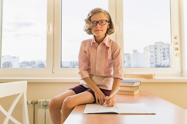 Colegial, menina de 8 anos, sentada à mesa com livros