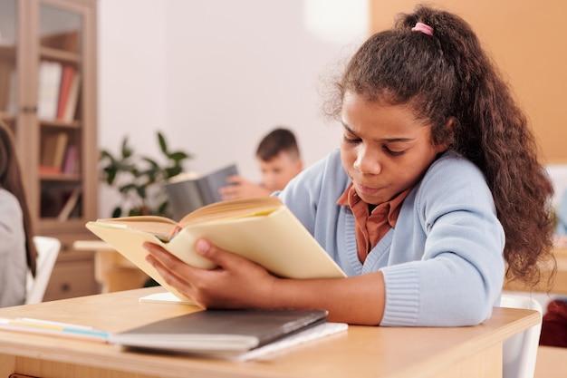 Colegial mestiça segurando um livro aberto e fazendo anotações enquanto está sentada na mesa na aula e trabalhando individualmente contra o colega de classe