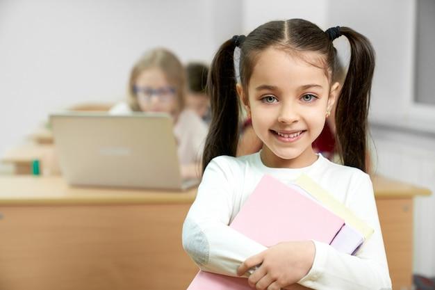 Colegial na sala de aula segurando livros, sorrindo.