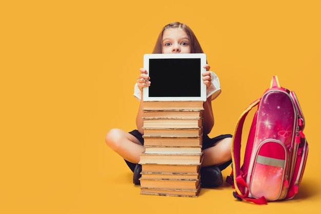 Colegial olha por trás de uma pilha de livros e o tablet olha para a câmera educação infantil