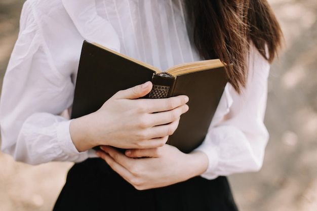Colegial ou universitária lendo um livro