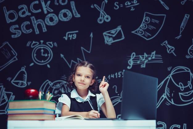 Colegial pensativa levantando o dedo indicador, sentada na mesa com laptop de educação a distância