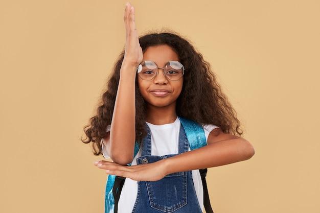 Colegial preta nerd sorridente confiante de óculos e mochila levantando a mão para responder a perguntas durante a aula contra bege
