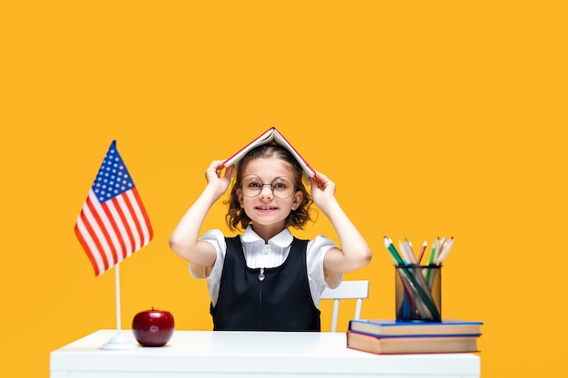 Colegial se divertindo sentada na mesa segurando um livro na cabeça, aula de inglês, bandeira dos eua
