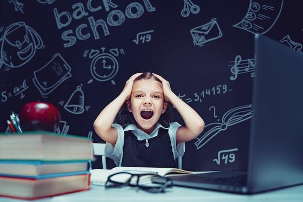 Colegial se senta à mesa com livros de laptop e um quadro-negro com fórmulas escolares no fundo w.