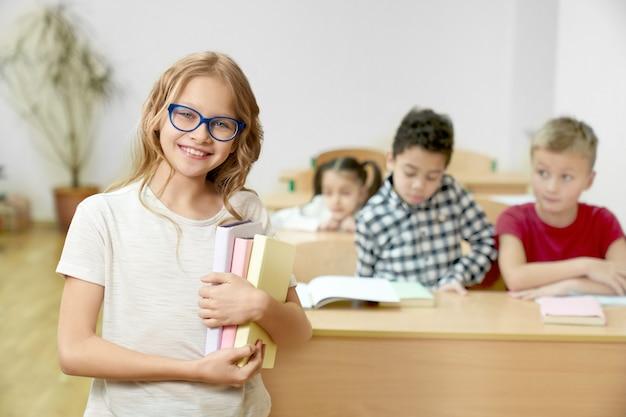 Colegial segurando livros, em pé na sala de aula, sorrindo.
