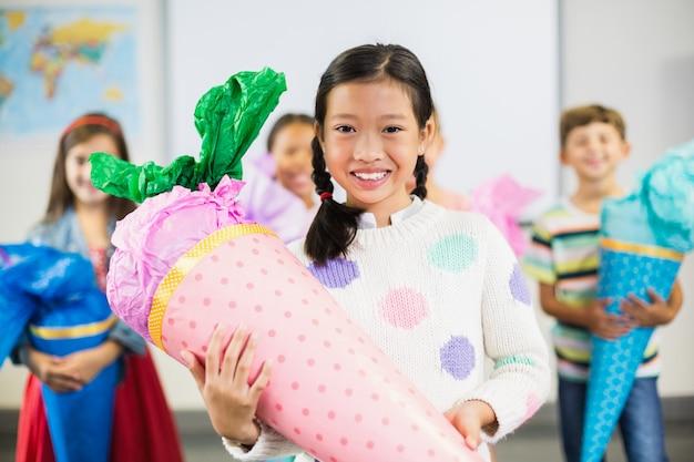 Colegial, segurando o presente na sala de aula