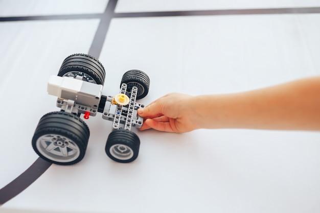Colegial segurando o robô construtor na aula de robótica.