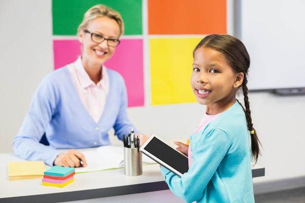 Colegial segurando o tablet digital em sala de aula