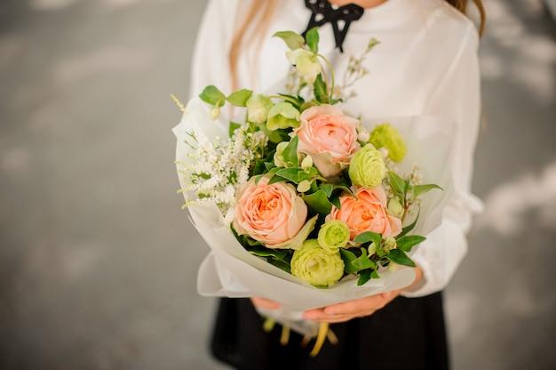 Colegial segurando um pequeno buquê de flores