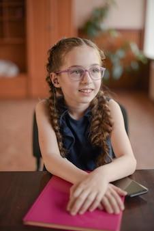Colegial sentada à mesa com livros didáticos em sala de aula. menina de vestido azul com tranças.