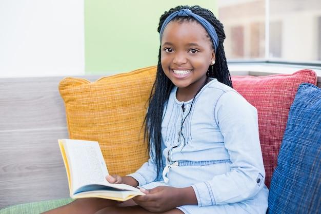 Colegial, sentado no sofá e livro de leitura