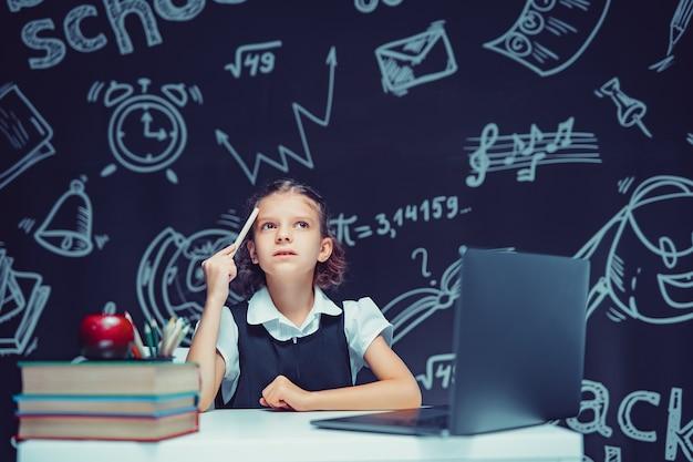 Colegial séria e pensativa levantando a caneta, sentada na mesa com laptop de educação a distância