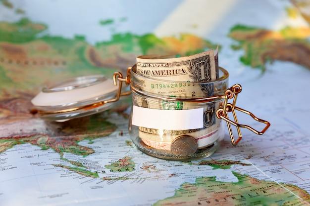 Coletando dinheiro para viajar. lata de vidro como moneybox com poupança em dinheiro (notas e moedas) no mapa