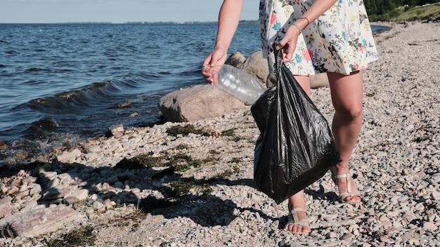 Coletando lixo de plástico em uma praia de seixos a menina coleta garrafas de plástico