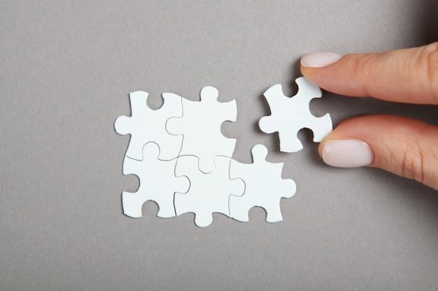 Colete a mão do quebra-cabeça e as peças do quebra-cabeça na mesa