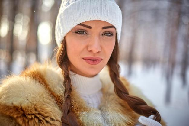 Colete de pele em uma bela jovem caucasiana em um inverno floresta ensolarada