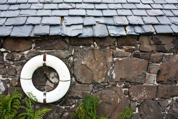 Colete salva-vidas em uma parede em uma vila de pescadores - escócia