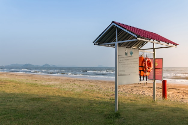 Coletes salva-vidas laranja pendurado em um rack com etiqueta de aviso para primeiros socorros em fundo de praia