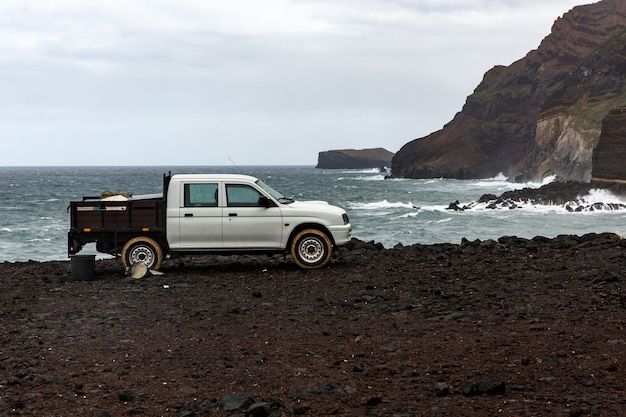 Coletor branco perto do oceano, costa rochosa.