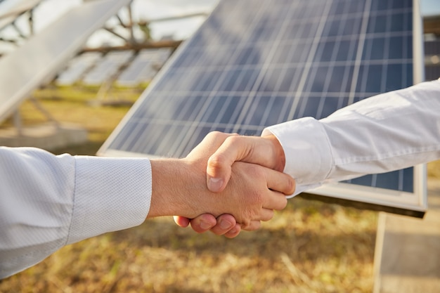 Colha parceiros de negócios masculinos anônimos apertando as mãos como símbolo de acordo, enquanto fica perto de painéis fotovoltaicos em uma estação de energia solar agrícola