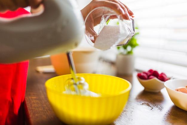 Colhe a mulher adicionando açúcar no creme chicoteado