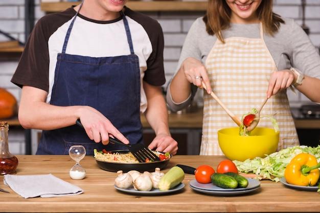 Colheita casal misturando legumes