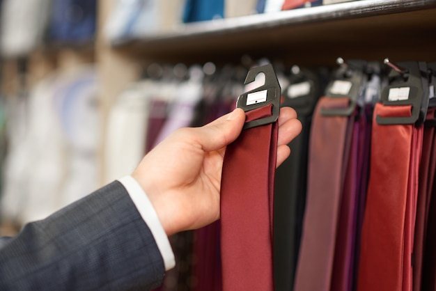 Colheita da mão do homem segurando a gravata do bordo na boutique.