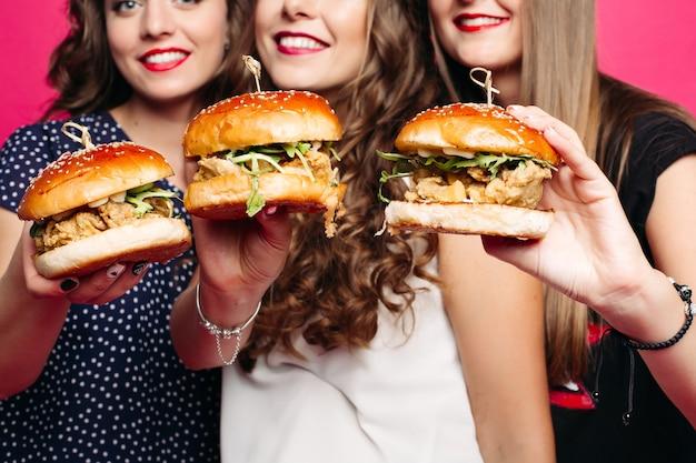 Colheita de amigos segurando deliciosos hambúrgueres com frango e legumes.