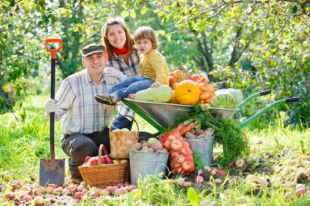 Colheita de família feliz em um jardim ao ar livre