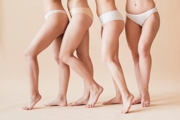 Colheita de figuras femininas descalças em cueca de pé atrás do outro