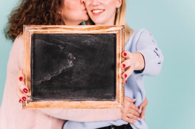 Colheita de mãe e filha segurando o quadro-negro
