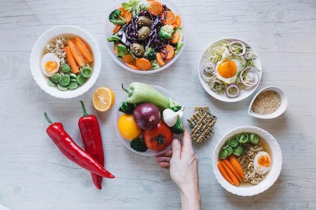 Colheita de mão colocando legumes perto de pratos