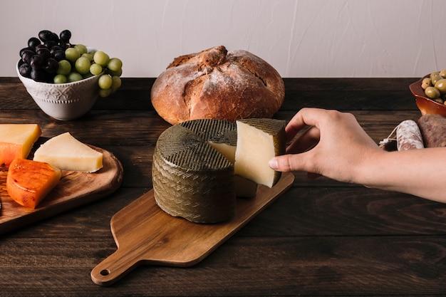 Colheita de mão tomando queijo perto de comida